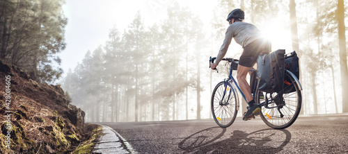 Cyclist on a bicycle with panniers riding along a foggy forest road - fototapety na wymiar