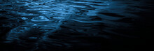 Reflection Of Light In Small Waves. Ripples On The Surface Of The Water. Wet, Fluid, Marble, Flowing Effect. Beautiful Dark Blue Green Background With Copy Space For Design. Web Banner.