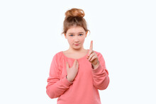 Cute Young Girl In Pink Casual Sweatshirt Points At Herself With Hand In Surprise. White Background