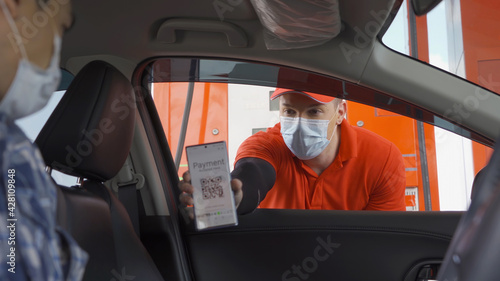 Fotografie, Tablou A customer, people, paying gas bill by scanning QR code, online payment, wearing a face mask at gasoline petrol station, an online payment option refuel oil