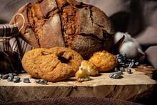 Pieces Of Broken Biscuits Lie On A Wooden Stump Next To Bread