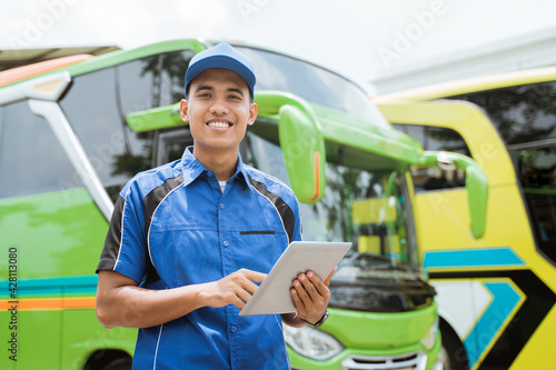 Foto a male bus crew member in uniform and a hat smiles at the camera while using a p