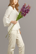 Young Blonde Lady In White Trousers And Blouse Is Holding Flowering Violet Gladioli. Romantic Lady Is Standing On The Gray Background And Looking At The Splendid Bouquet.