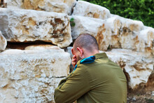 Israeli Soldier Crying In Front Of The Graves Of Fallen Soldiers. Concept: Israeli Soldiers, Israel Memorial Day - Yom HaZikaron, Holocaust Remembrance Day - Yom Hashoah, Israel Independence Day