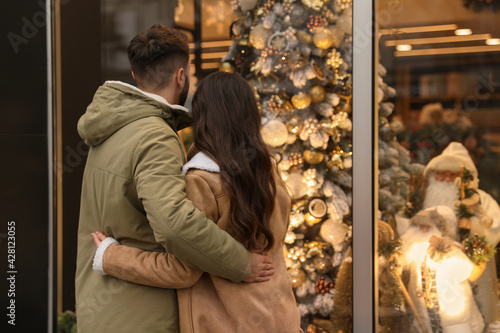 Fototapeta Lovely couple near store decorated for Christmas outdoors, back view obraz