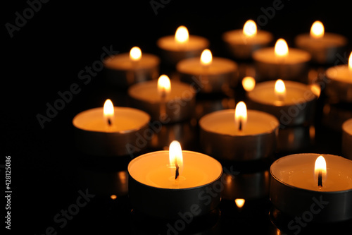Obraz Many burning tea candles on black background, closeup - fototapety do salonu