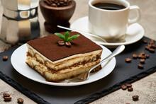 Portion Of Traditional Italian Tiramisu Dessert And Mocha Coffee Maker On Grey Concrete Background