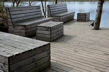 Floating Walkway Made Of Wood Planks. Narrow Curved Leads Above The Lake Water. Has No Railings. More Design Sidewalk Made Of Individual Circular Boards.