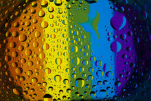 Drops Of Water On The Glass, With The Reflection Of The Rainbow.