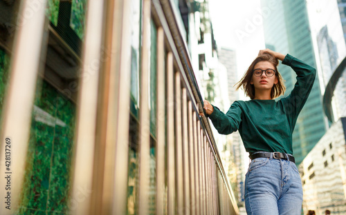 Canvas Portrait of a hipster girl with short hairstyle, looking at the camera posing on urban street, at buildings background