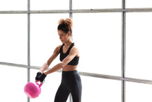 Close Up Of Young Beautiful Woman Doing Crossfit Russian Swing In A Gym With A Pink Kettlebell. White Background. Horizontal View