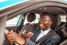 Calling By Driving. Risky Driver Using Phone While Driving. Close Up Of A Handsome Young Businessman Talking On Mobile Phone In His Car. Businessman Talking On The Phone While Driving A Car