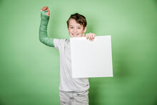 Cool School Boy With Green Hand Plaster Holding White Board In Front Of Green Background