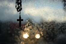 Rosary, Cross, Wet Window And Lights Of An Oncoming Car