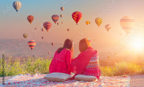 Fotografie, Obraz Hot air balloon flying over spectacular Cappadocia - Japanese girls watching hot