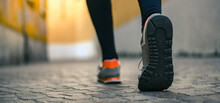 Close Up Of Male Feet Walking During Workout. Legs Of Man Run In The City And Jogging Alone. Crocodile View Of A Runner Doing Sport Activity In A Deserted Town. Closeup Of Running Shoes Stepping.