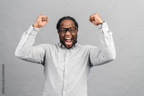 Fotografia Excited African-American guy wearing smart casual shirt celebrating victory, rai
