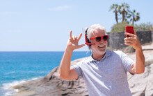 Attractive Crazy Senior Man Taking Selfie At The Sea, Wearing Red Headphones And Sunglasses. Carefree Retired Having Fun Using Smartphone Playlist Apps