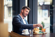 Confident Businessman Have A Lunch In Restaurant