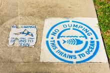 No Dumping Drains To Ocean Warning Sign Guards Drain Inlet Near Storm Drain.