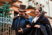 Couple Wearing Traditional Victorian Clothes, Man And Woman Walking And Talking. Fashion And Trends Of Previous Epochs And Times. Male Wearing Cloak, Female In Dress And Hat.