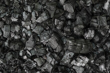 Black And Gray Pieces Of Burnt Branches, In The Remains Of An Extinguished Fire. Charred Branches And Big Chunks Of Charcoal On The Ground. Carbonized Wood. Photo.