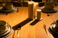 Table Set In A Minimalist Style With Candles. The Geometric Dishware And The Light Effects Remind Of A Still Life Painting By Giorgio Morandi Or Of CGI Rendering.