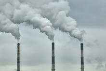 Three Chimneys Of A Thermal Power Plant On The Background Of A Cloudy Sky