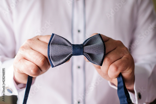 Foto Blue bow tie in the hands of the groom