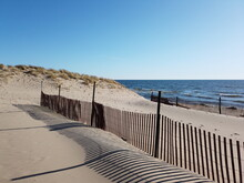 Snow Fence Along The Beach With Dune And Blue Sky