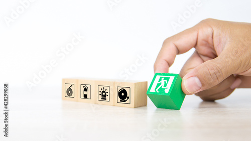 Obraz na plátně Fire exit,  Close-up hand choose wooden toy block stack with door exit sing or fire escape icon with fire extinguisher and emergency protection symbol for safety prevent and rescue