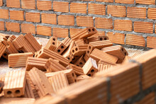 A Large Pile Of Orange Bricks Is Prepared For The Construction Of The Walls Of The Building.