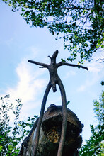 Wooden Snag In The Form Of A Pagan Idol Against The Blue Sky