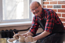 Senior Male Potter Creating Bowl In Pottery Workshop.