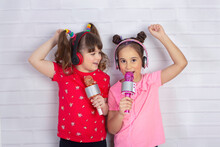 Two Little Girl With A Microphone  Singing Together And Playing