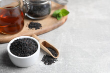 Black Sesame Seeds And Oil On Grey Table, Space For Text