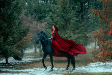 Medieval Woman Princess In Red Dress Sits Astride Black Steed Horse. Girl Rider In Vintage Cloak Cape Train Flies In Wind Motion. Background Green Trees Spruce Forest Spring Winter Nature Melted Snow