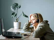 Teenage Girl In Headphones With Microphone Studying Online At Home, Remote Learning And Home Schooling
