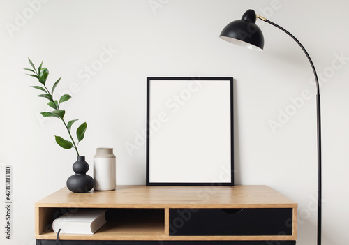 Fototapeta Blank picture frame mockup on white wall. White living room design. View of modern scandinavian style interior with artwork mock up on wall. Home staging and minimalism concept obraz