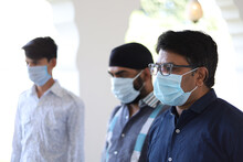 Selective Focus Shot Of An Indian Man With Eyeglasses Wearing Face Mask Standing Outside The Clinic
