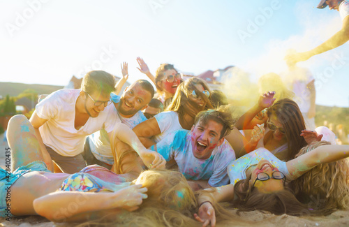 Group of people have fun at the holi festival of colors. Smiling faces in colorful powder. Celebrating traditional indian spring holiday. Party, vacation concept. Friendship and celebration concept. - fototapety na wymiar
