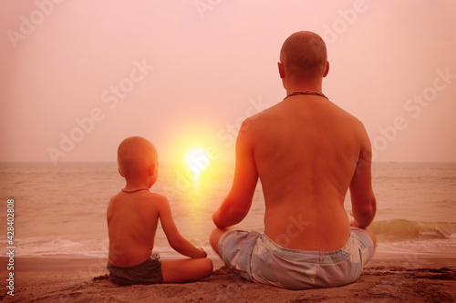 Papel de parede Father and son sit in the evening on the ocean and look out into the distance to the setting sun