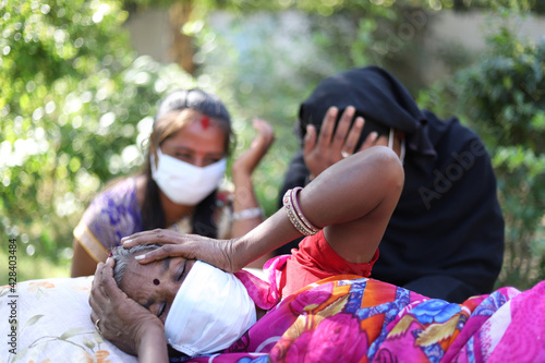 Shallow focus shot of an old Indian woman wearing a facemask, lying down in pain - fototapety na wymiar