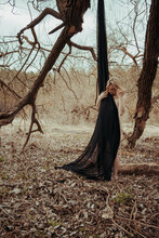 Beautiful Young Nude Sexy Blonde Woman With A Black Cloth, Stands Against The Background Of Dry Lifeless Grass