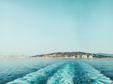Wave Wake From Sailing Ship With Port And Ropeway Of Barcelona, Spain In The Background