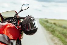 Black Motorcycle Helmet Hanging On The Handlebars Of The Motorcycle