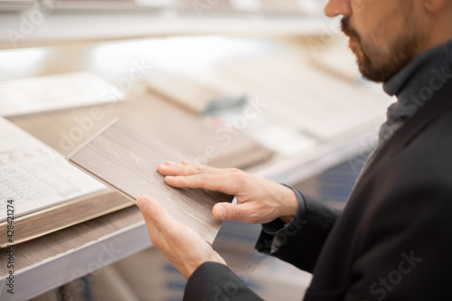 Obraz .Middle age man choosing floor laminate for his home. Difficult decision which to buy - fototapety do salonu