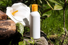 Big White Bottle With Yellow Cap For Beauty Product Mock Up Standing In Under The Sun In The Natural Environment. Bottle Colors Correspond The Color Of Calla Lily Flower Standing Behind The Bottle