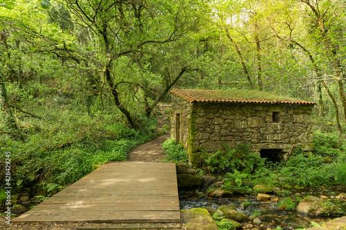 Billede på lærred Old boathouse on the river with a wooden walkway