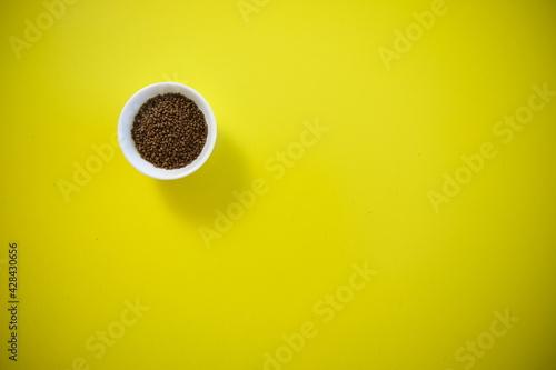 Fototapeta Tatar buckwheat tea in a white bowl. On a yellow background. obraz